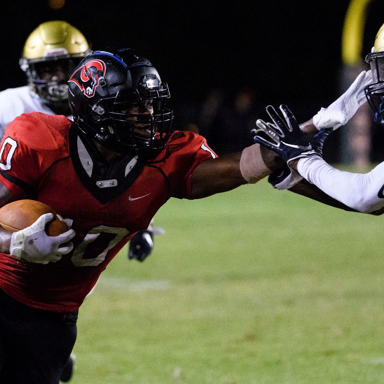 Hillcrest's Quendarius Jefferson (10) gives a stiff-arm to Spartanburg's Chris Manning (15) during the Rams' 24-7 loss Friday at Chandler Stadium.