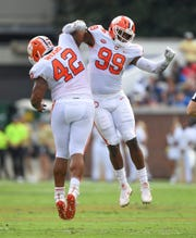 Clemson defensive lineman Christian Wilkins (42) celebrates a defensive stop against Georgia Tech with defensive lineman Clelin Ferrell (99) during the 1st quarter at Georgia Tech's Bobby Dodd Stadium Saturday, September 22, 2018.