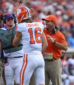 Clemson head coach Dabo Swinney celebrates with quarterback Trevor Lawrence (16) after he threw a TD to wide receiver Hunter Renfrow (13) during the 2nd quarter at Georgia Tech's Bobby Dodd Stadium Saturday, September 22, 2018.