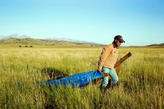 In a Sept. 5, 2018 photo, Peruvian migrant worker Jose Luis Munoz Anco moves irrigation dams along the ditches in the grassland east of the Crazy Mountains near Livingston, Mont. In Montana, he makes more than double the wage for similar work in Peru, allowing his wife to be home with their children even if dad is thousands of miles away, working 48 hours a week, six days a week, at $11.60 per hour, providing for his family back home in Peru. (Nate Howard/Livingston Enterprise via AP)