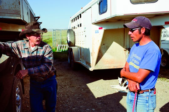In a Sept. 5, 2018 photo, Roger Indreland, left, and Peruvian migrant worker Jose Luis Muñoz Anco discuss the day's work near Livingston, Mont. Here in Montana, he makes more than double the wage for similar work in Peru, allowing his wife to be home with their children even if dad is thousands of miles away, working 48 hours a week, six days a week, at $11.60 per hour, providing for his family back home in Peru.(Nate Howard/Livingston Enterprise via AP)