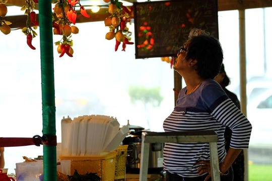 A vendor adjusts the lighting at her stand while awaiting festival patrons.