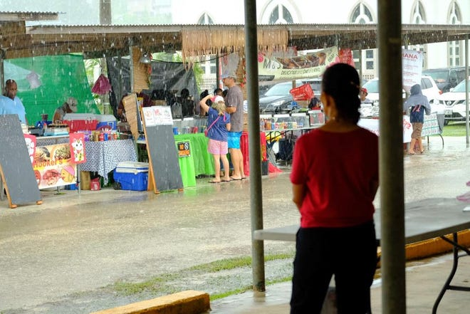 A festival goer looks on at the sudden downpour at the Mangilao Donne' Festival grounds. Weather officials estimated the island would receive up to 8 inches of rain throughout the weekend.