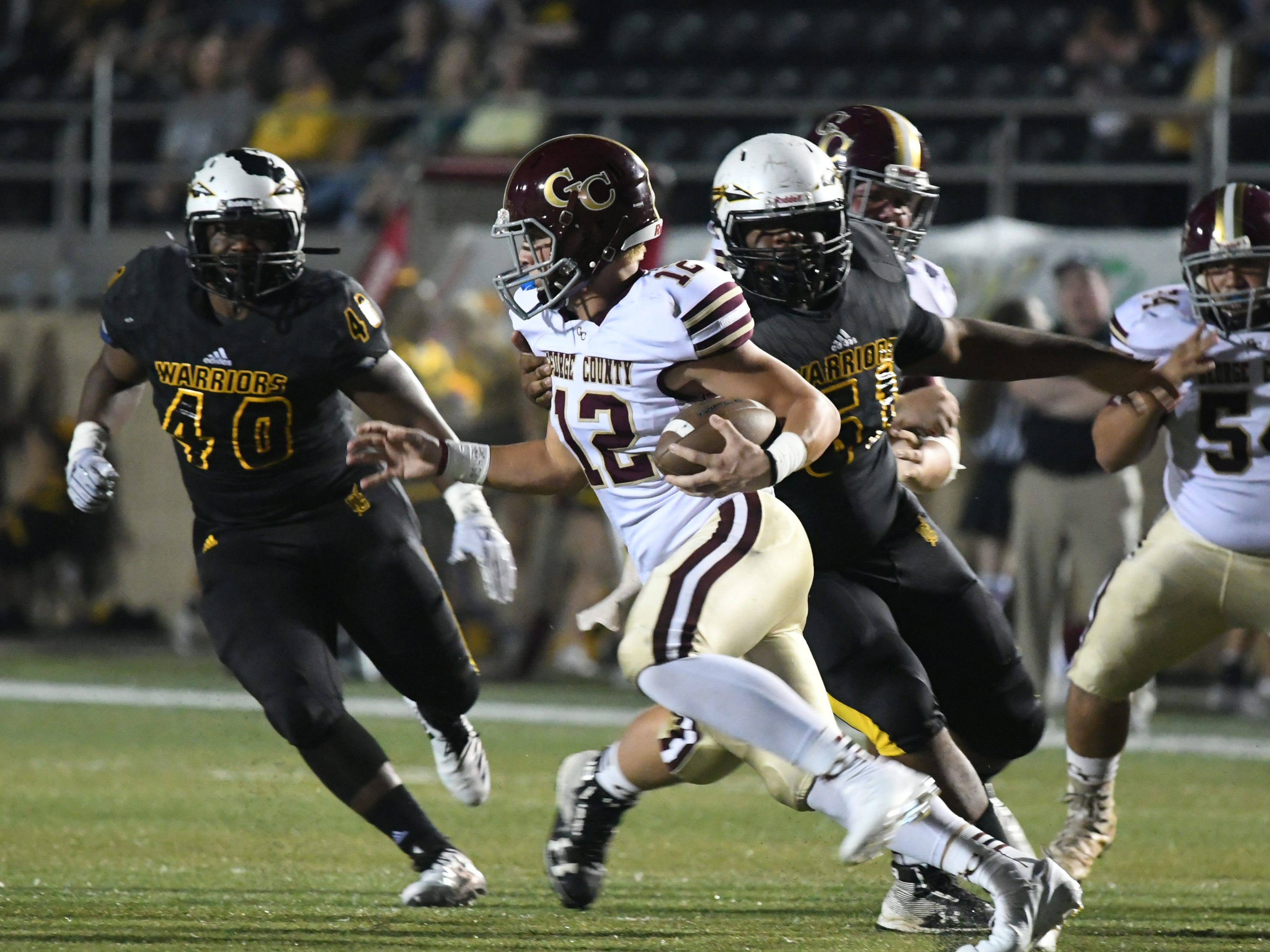 Oak Grove defensive players attempt to tackle George County quarterback Jonathan Havard in Hattiesburg on Friday, September 21, 2018.