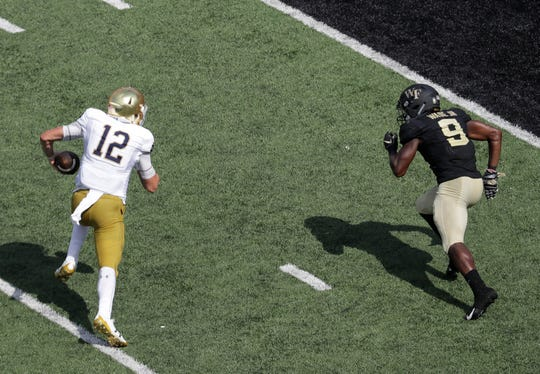 Notre Dame's Ian Book (12) runs past Wake Forest's Chuck Wade Jr. (9) for a touchdown in the second half of an NCAA college football game in Winston-Salem, N.C., Saturday, Sept. 22, 2018. (AP Photo/Chuck Burton)