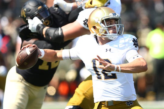 Notre Dame Fighting Irish quarterback Ian Book (12) looks to pass int he first quarter against the Wake Forest Demon Deacons at BB&T Field.