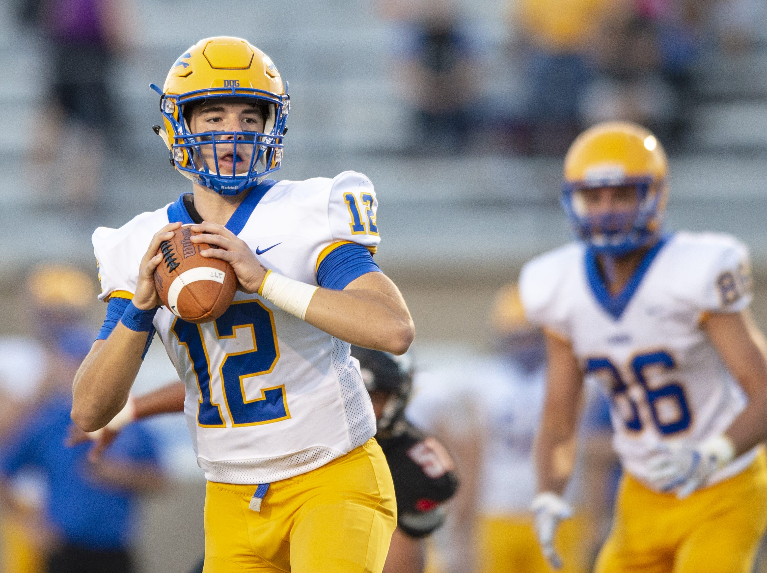 Carmel High School senior Tyler Trent (12) drops back to pass during the first half of action. North Central High School hosted Carmel High School in IHSAA varsity football action, Friday, Sept. 21, 2018.