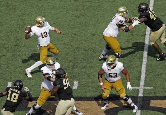 Notre Dame's Ian Book (12) looks to pass against Wake Forest in the second half of an NCAA college football game in Winston-Salem, N.C., Saturday, Sept. 22, 2018. (AP Photo/Chuck Burton)