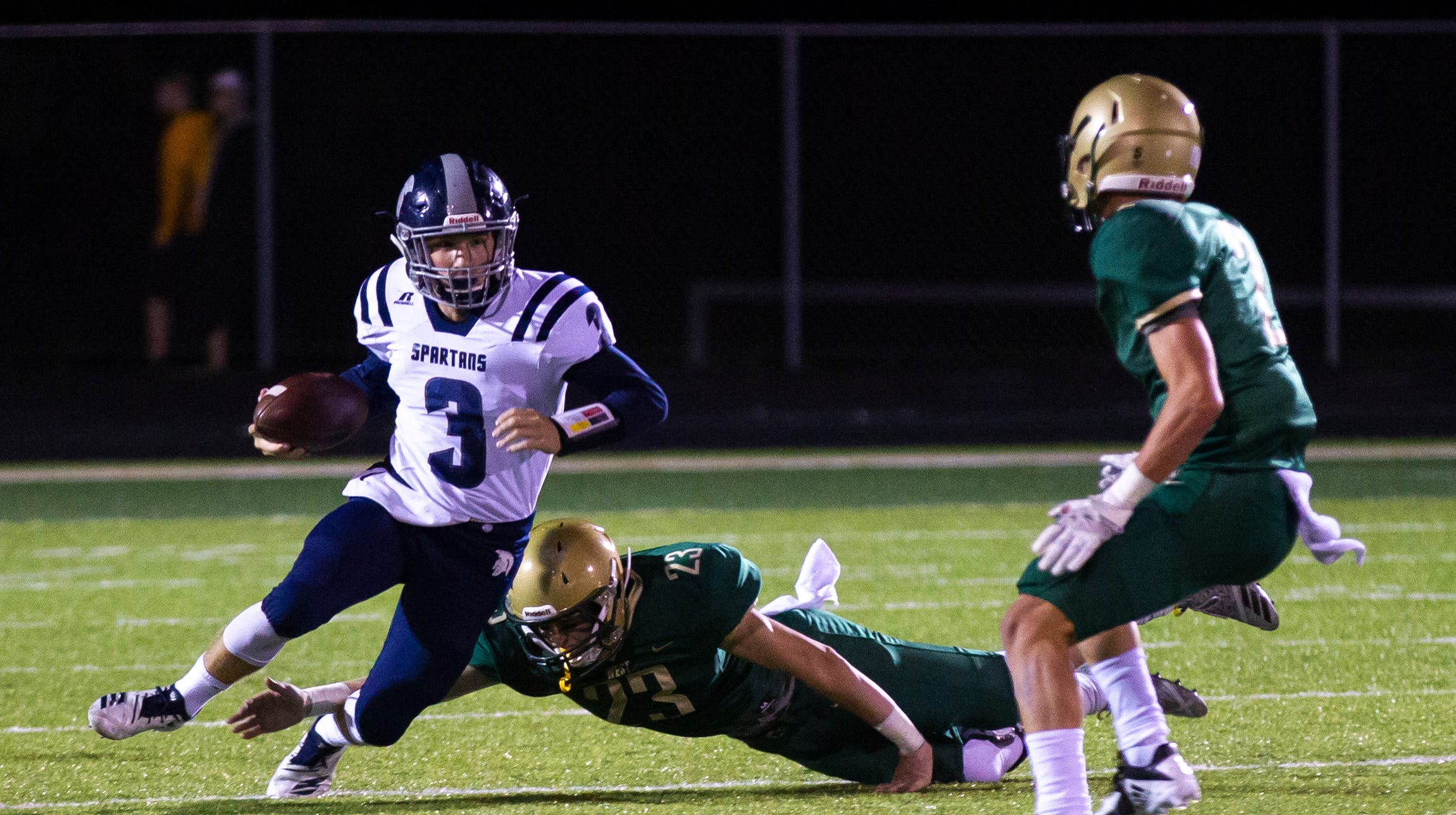 Pleasant Valley's Max Slavens (3) attempts to avoid a sack from Iowa City West's Brendan Mott(23) during a Class 4A varsity football game on Friday, Sept. 21, 2018, at Trojan Field in Iowa City.