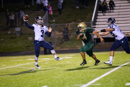 Pleasant Valley quarterback Max Slavens (3) attempts to get a pass away while Iowa City West's Landon Green (44) closes in during a Class 4A varsity football game on Friday, Sept. 21, 2018, at Trojan Field in Iowa City.