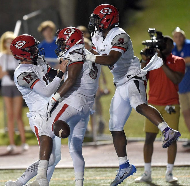 Clinton's Desmyn Baker (5) gets congratulations for his touchdown from Hunter Hulsey (17) and EJai Mason (3)  on Friday, September 21, 2018, at Madison Central High School in Madison, Miss.
