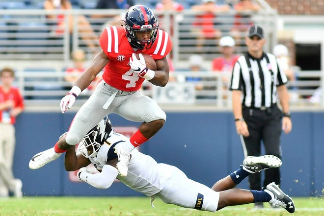 Ole Miss running back Tylan Knight (4) avoids a tackle by Kent State Golden Flashes cornerback Jamal Parker (7) during the second quarter of the Rebels' 38-17 win at Vaught-Hemingway Stadium Saturday. Mandatory Credit: Matt Bush-USA TODAY Sports