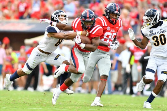 Sep 22, 2018; Oxford, MS, USA; Mississippi Rebels running back Tylan Knight (4) runs the ball as he is defended by Kent State Golden Flashes safety Elvis Hines (8) during the second quarter at Vaught-Hemingway Stadium. Mandatory Credit: Matt Bush-USA TODAY Sports
