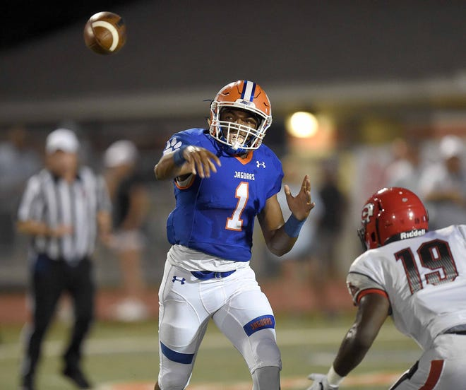 Madison Central's  Jimmy Holiday (1) throws over the middle against Clinton on Friday, September 21, 2018, at Madison Central High School in Madison, Miss.