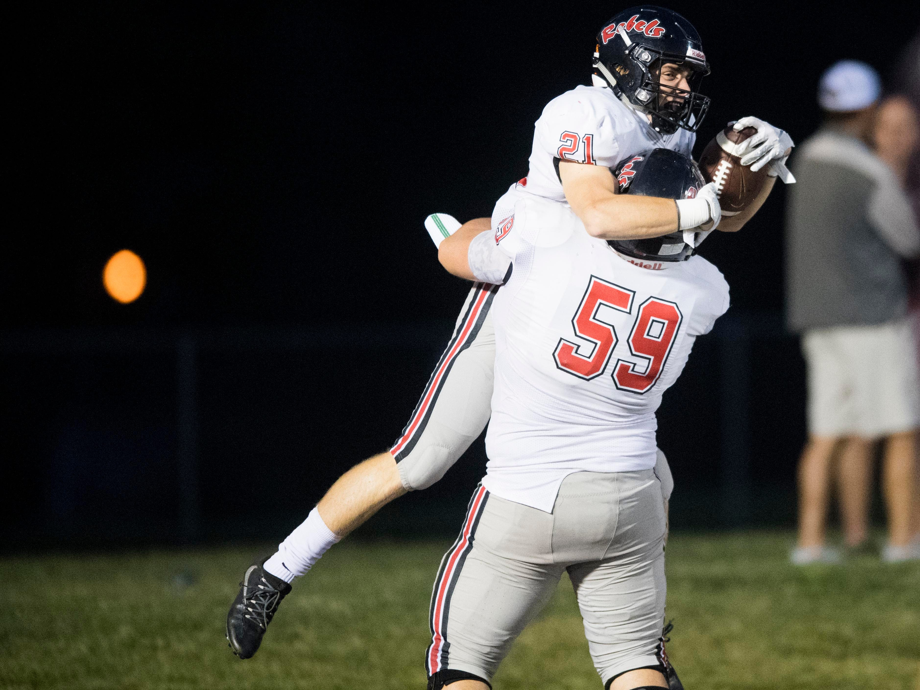 Maryville's Bryson Teffeteller (21) and Jacob Barbee (59) celebrate after Teffeteller scored a touchdown in the football game against Fulton Maryville on Friday, September 21, 2018.