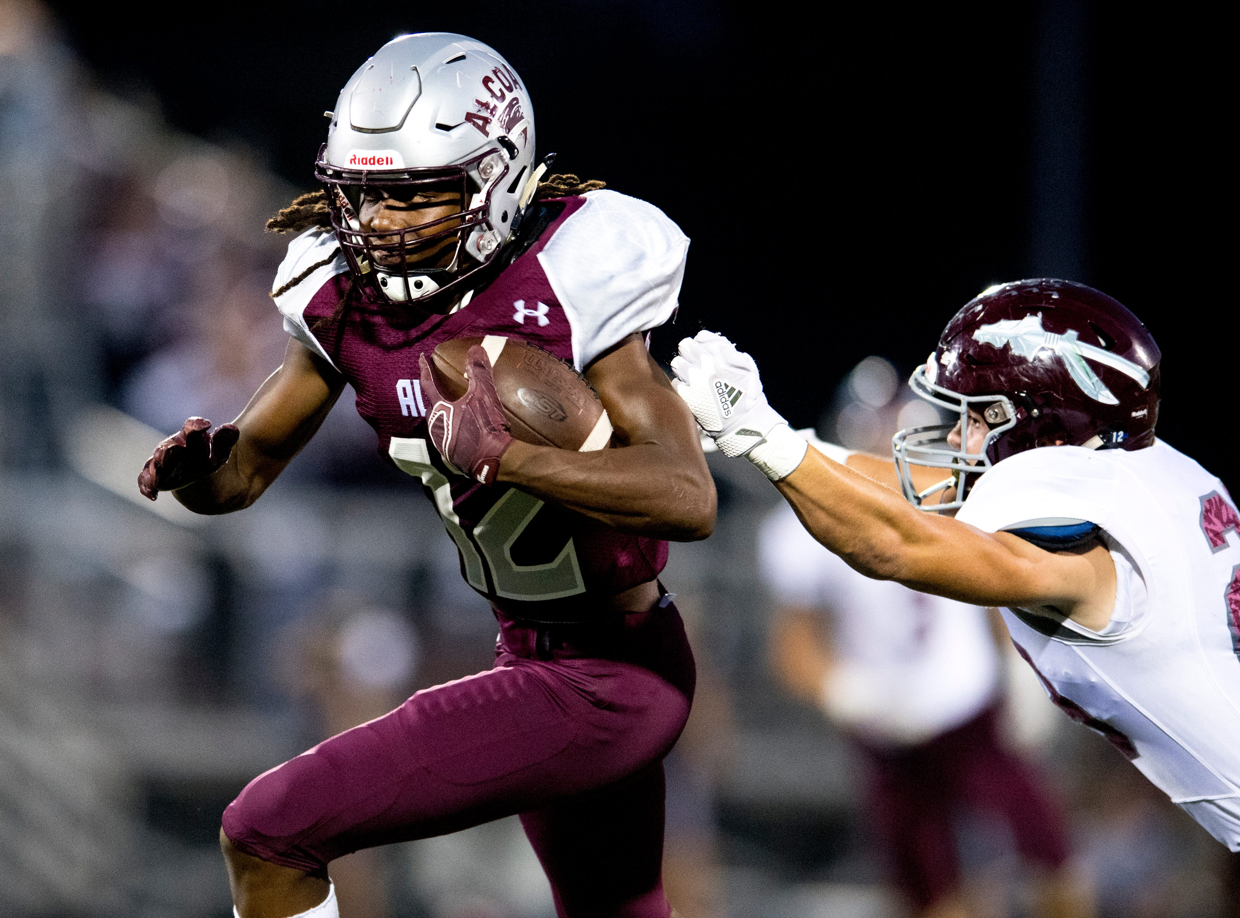 Alcoa's Isiah Cox (12) runs with the ball as Dobyns-Bennett's Jackson Martin (29) defends during a game between Alcoa and Dobyns-Bennett at Alcoa High School in Alcoa, Tennessee on Friday, September 21, 2018.