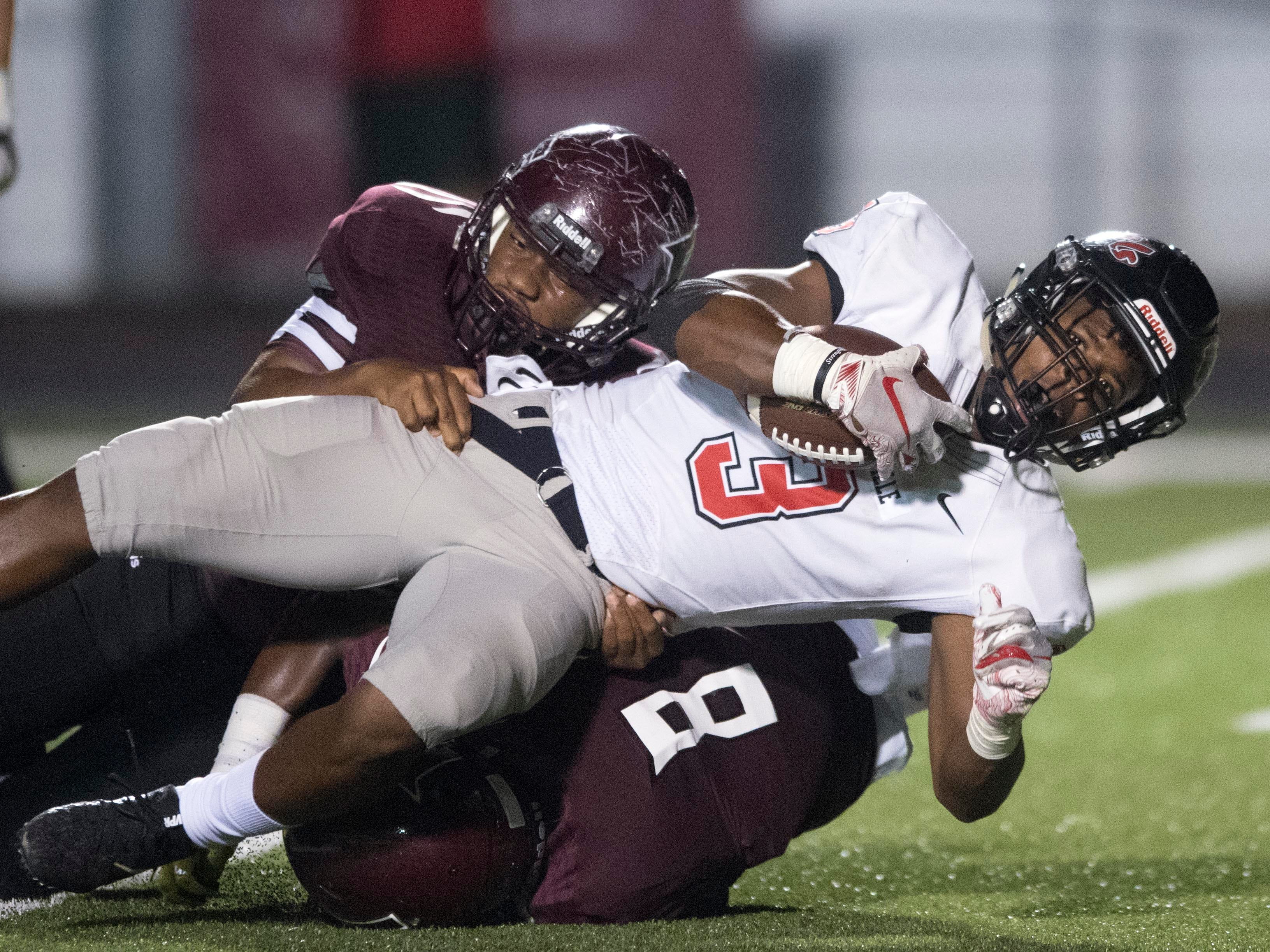Maryville's A.J. Davis (3) goes it taken down by Fulton's Terrence Brown (22) and DaShaun McKinney (8) in the football game at Fulton on Friday, September 21, 2018.