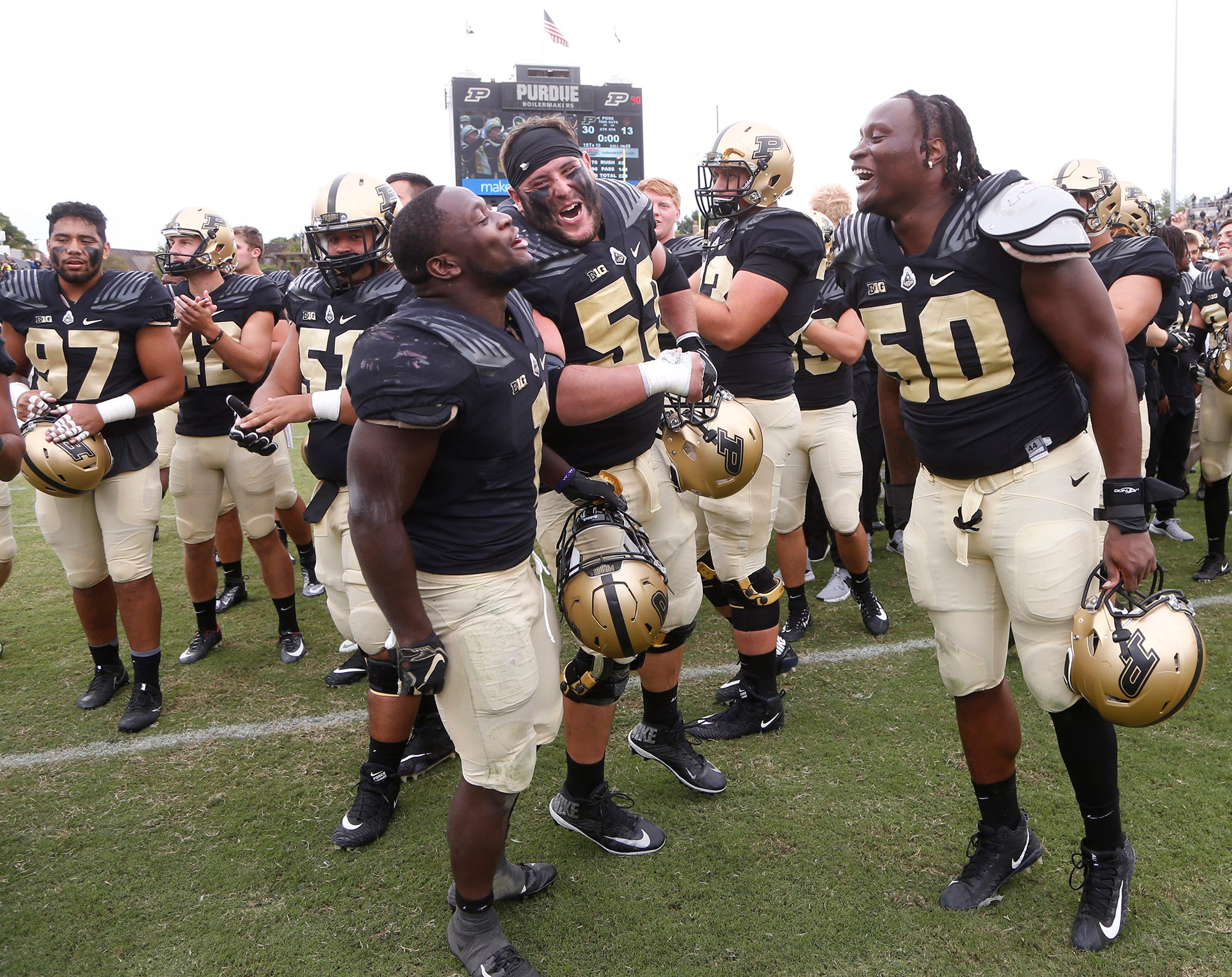 D. J. Knox, from left, Kirk Barron and Keiwan Jones celebrate after Purdue defeated Boston College 30-13 Saturday, September 22, 2018, in Ross-Ade Stadium.