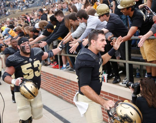 Purdue quarterback David Blough and center Kirk Barron slap hands with the Purdue faithful after the Boilermakers defeated Boston College 30-13 Saturday, September 22, 2018, in Ross-Ade Stadium.
