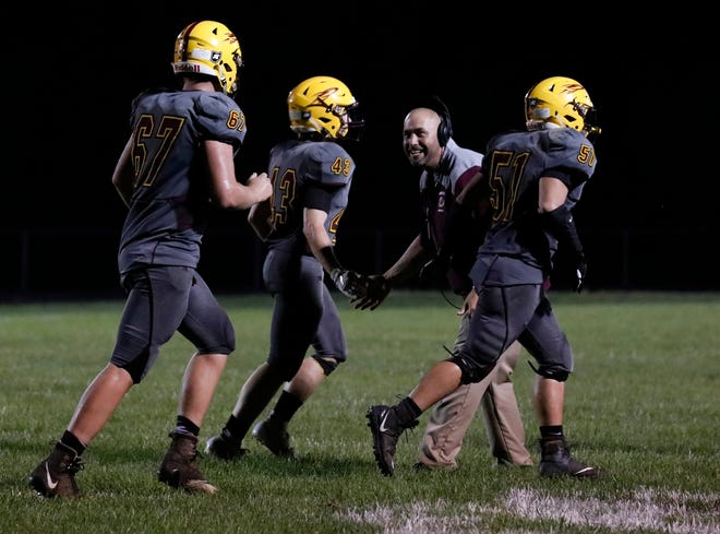 Berne Union head coach Tony Hurps congratulates his players as they come off the field during the Rockets' 27-13 Mid-State League-Cardinal Division win over Fisher Catholic.