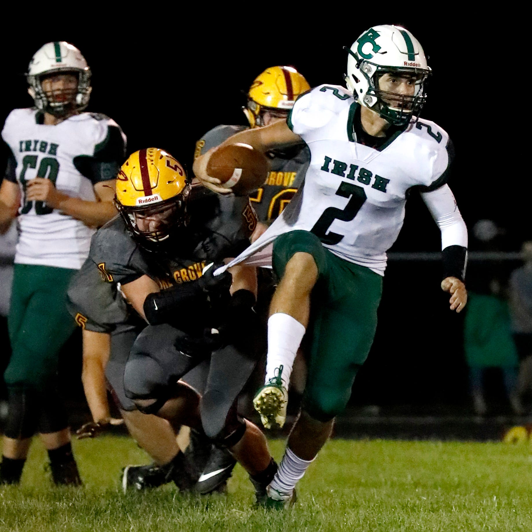 Berne Union's Lewie Stephens grabs the jersey of Fisher Catholic quarterback Kaden Starcher before tackling him Friday, Sept. 21, 2018, at Berne Union High School in Sugar Grove. The Rockets defeated the Irish 27-13.