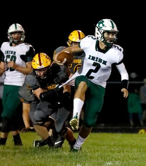 Fisher Catholic quarterback Kaden Starcher breaks away from a Berne Union defender during a 2018 game. Those two teams, along with Fairfield Christian Academy, will be forced to find another game due to Zanesville Rosecrans cancelling football due to lack of numbers.