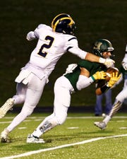 Howell's Shane Sovik gets position in front of receiver Logan Tobel to grab the first of his two interceptions in a 42-14 victory over Hartland on Friday, Sept. 21, 2018.