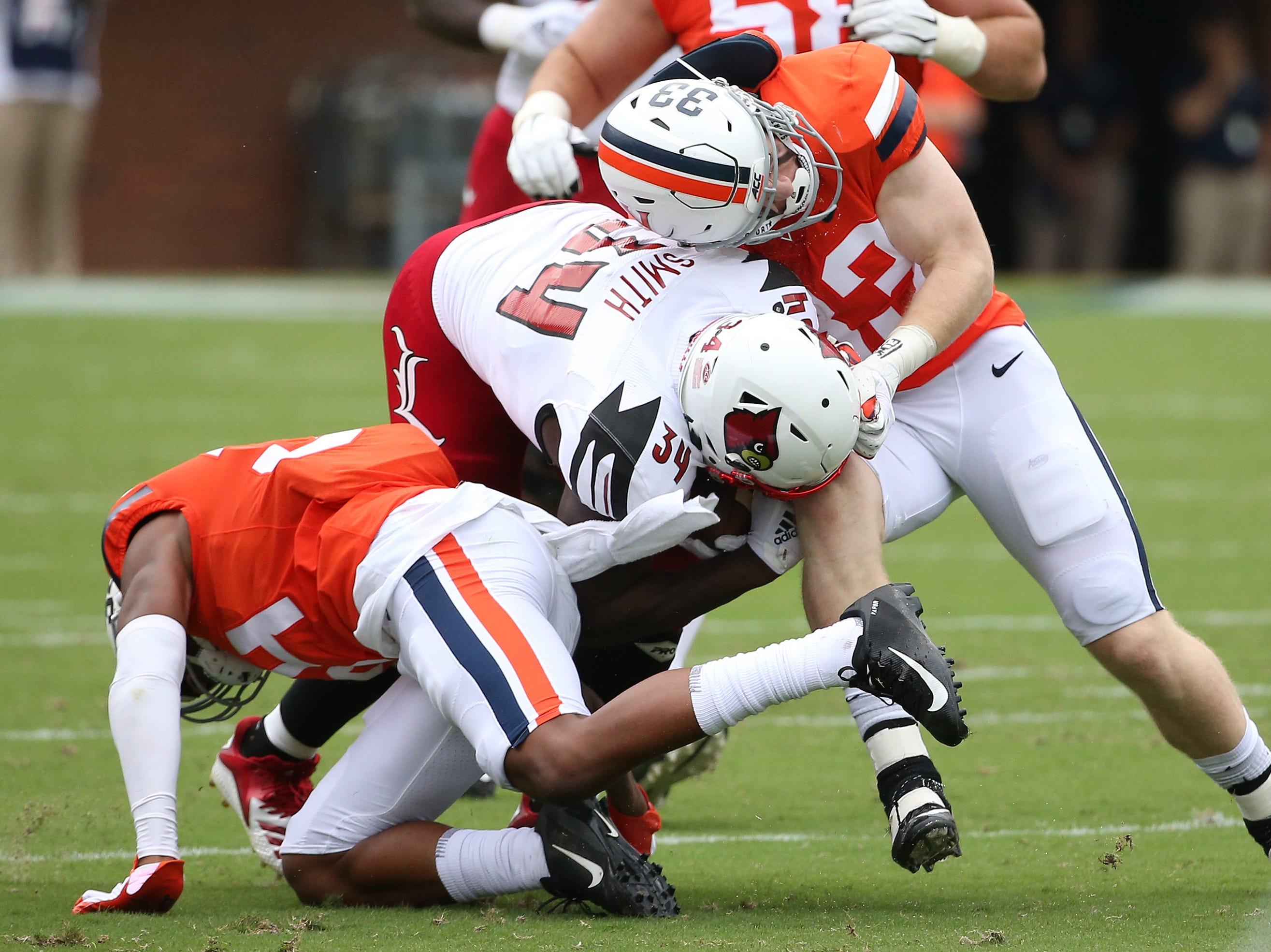 Sep 22, 2018; Charlottesville, VA, USA; Louisville Cardinals running back Jeremy Smith (34) is tackled by Virginia Cavaliers safety CJ Epps (39) and Cavaliers cornerback Bryce Hall (34) in the first quarter at Scott Stadium. Mandatory Credit: Geoff Burke-USA TODAY Sports