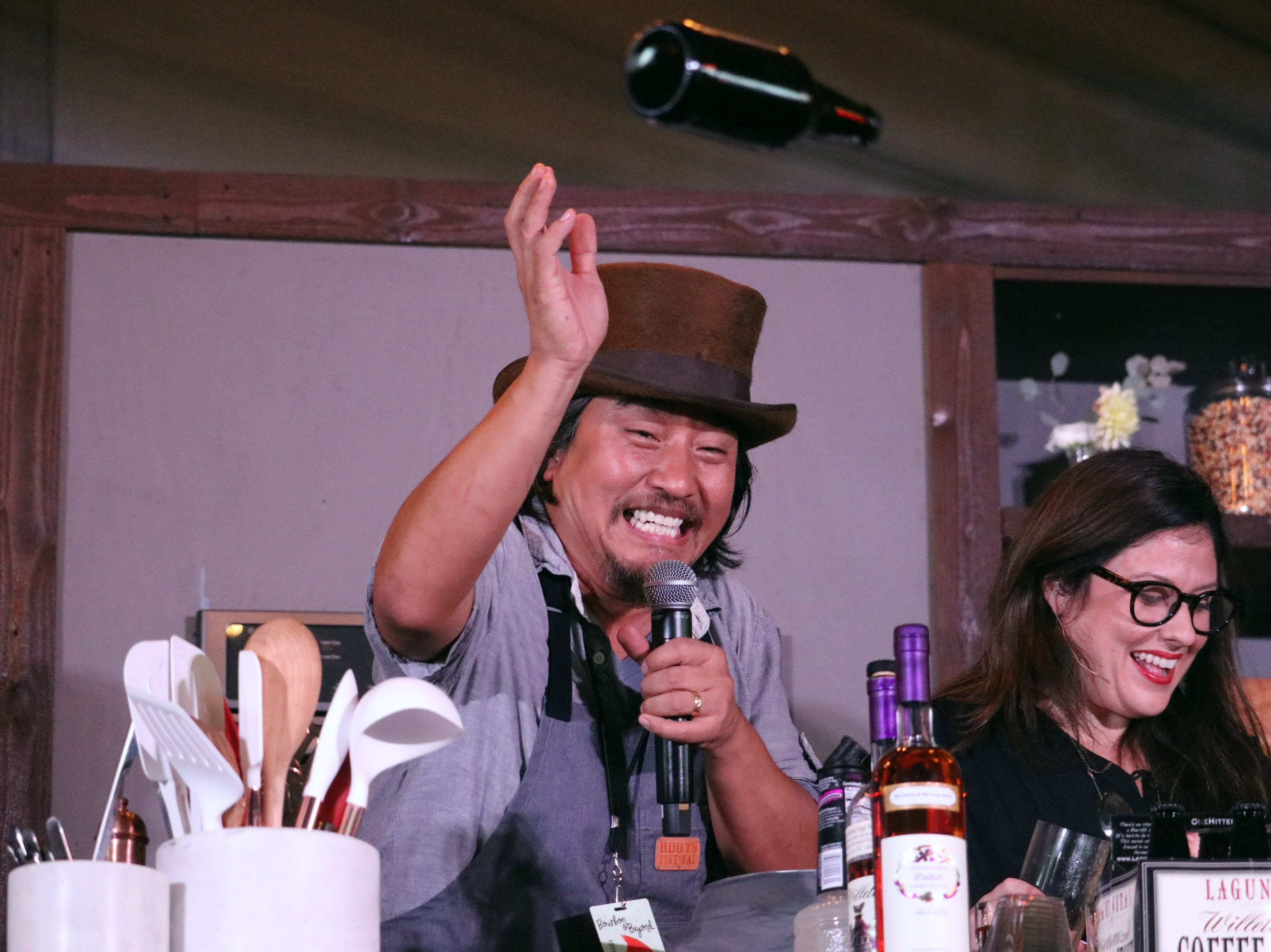 Chef Edward Lee tosses a bottle of beer into the audience during a cooking demonstration at the 2018 Bourbon & Beyond festival.
