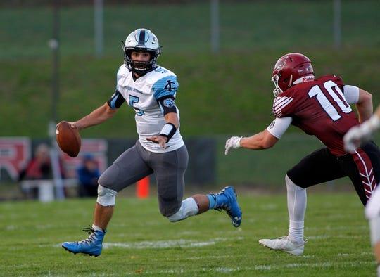 Lansing Catholic quarterback Josh Kramer, left, scrambles against Portland's Bobby Brandsen, Friday, Sept. 21, 2018, in Portland, Mich. Portland won 16-8.