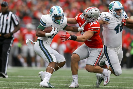 Tulane running back Amare attempts to stiff arm Ohio State linebacker Tuf Borland (32) .