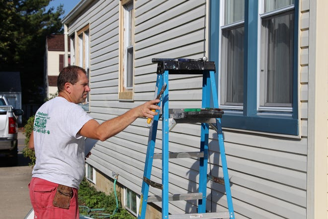 Paul Anderson replaces the window trim at a Merchant Avenue house where he is building an addition onto the back of the house.