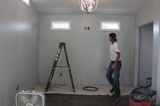 Danny Lewis, of Anderson's Home Improvement, paints a room addition that he helped construct on a Merchant Avenue house.