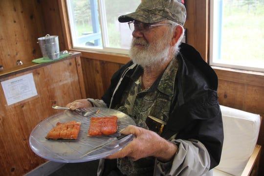 Wayne Haag of Alagnak Lodge in Alaska offers freshly smoked salmon to guests.