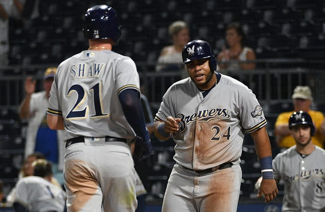 The Brewers' Travis Shaw is greeted at home plate by teammate Jesus Aguilar after hitting a two-run homer in the sixth inning.