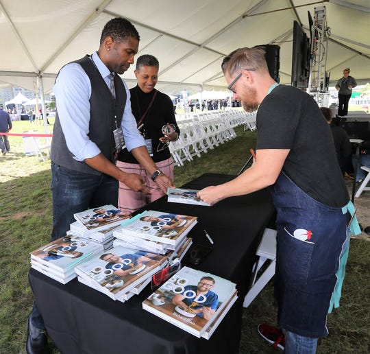 "Gerard and Renee Washington get their cookbook signed by ""Top Chef"" winner Richard Blais (right) at the Milwaukee Journal Sentinel Wine & Food Experience."