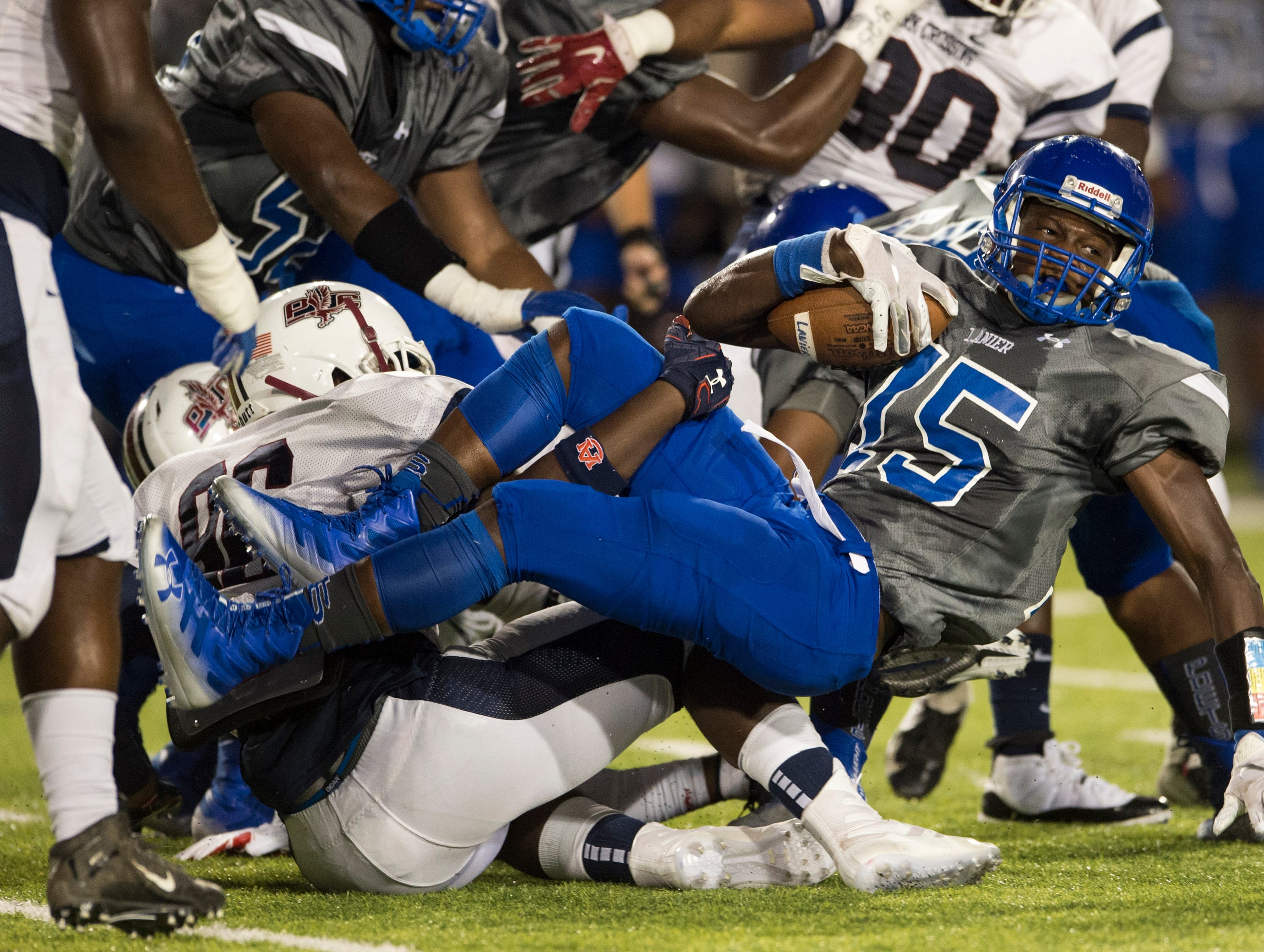 Lanier's Jacory Merritt (15) falls over defenders as he runs the ball at Cramton Bowl in Montgomery, Ala., on Friday, Sept. 21, 2018. Lanier leads Park Crossing 14-7 at halftime.