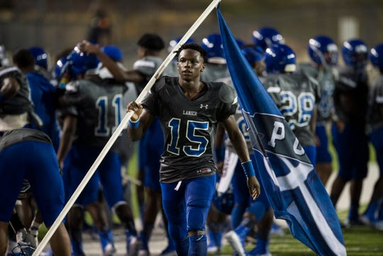 Lanier's Jacory Merritt (15) caries the Poets flag after the game at Cramton Bowl in Montgomery, Ala., on Friday, Sept. 21, 2018. Lanier defeated Park Crossing 35-28.