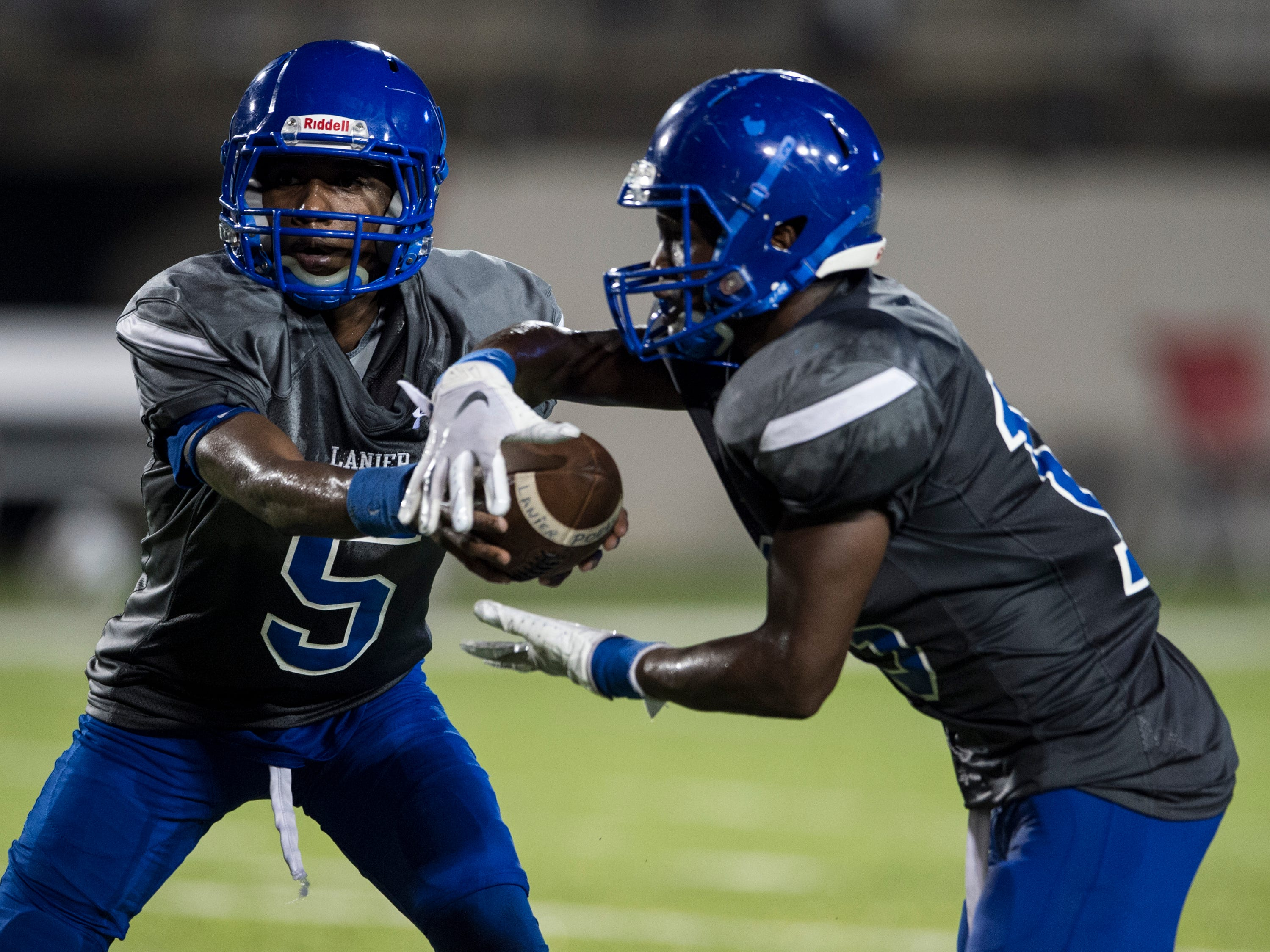 Lanier's Marquarius Moore (5) hands the ball off to Jacory Merritt (15) at Cramton Bowl in Montgomery, Ala., on Friday, Sept. 21, 2018. Lanier defeated Park Crossing 35-28.