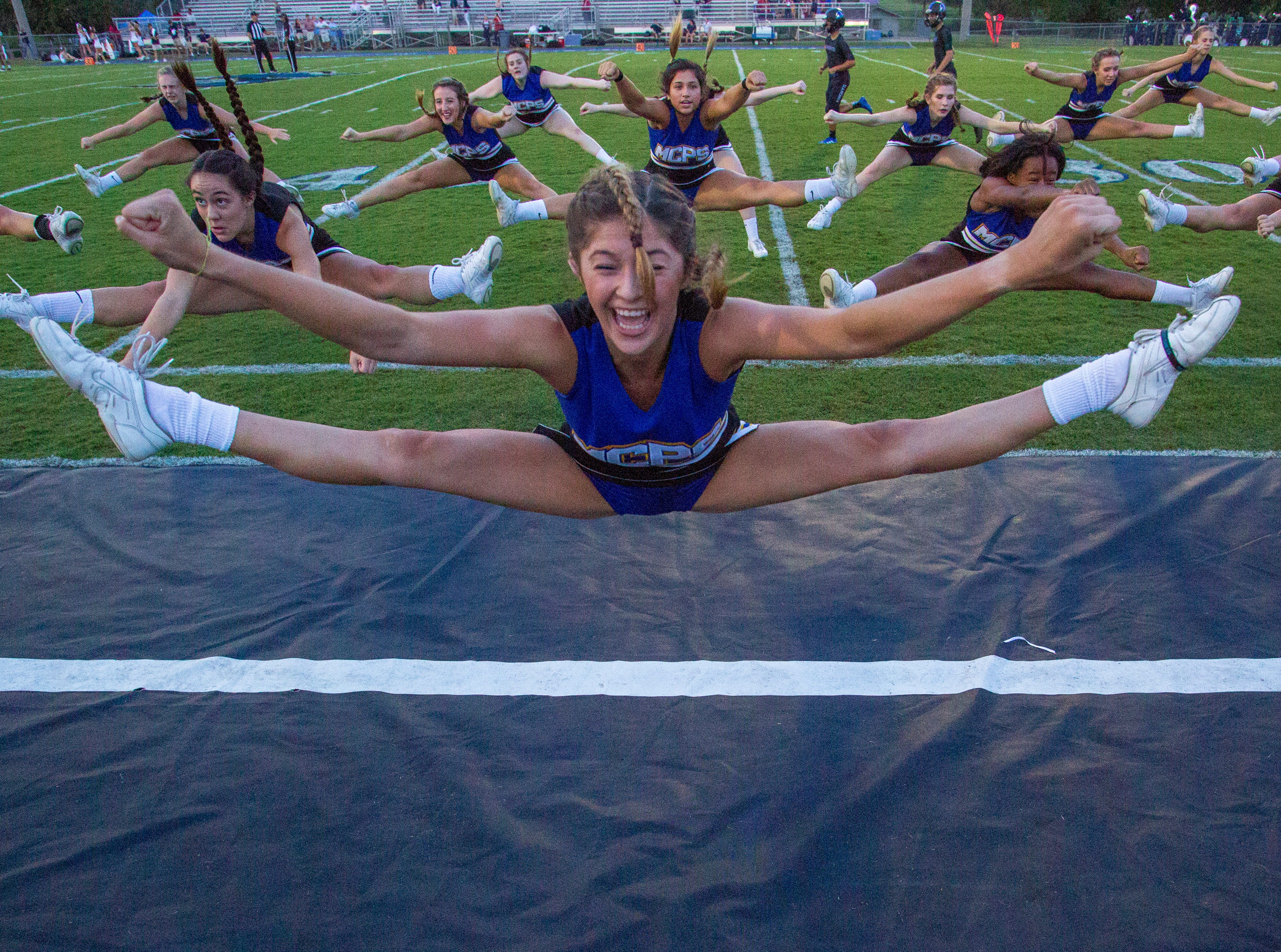 The Montgomery Catholic cheerleaders warm up with some toe touches.