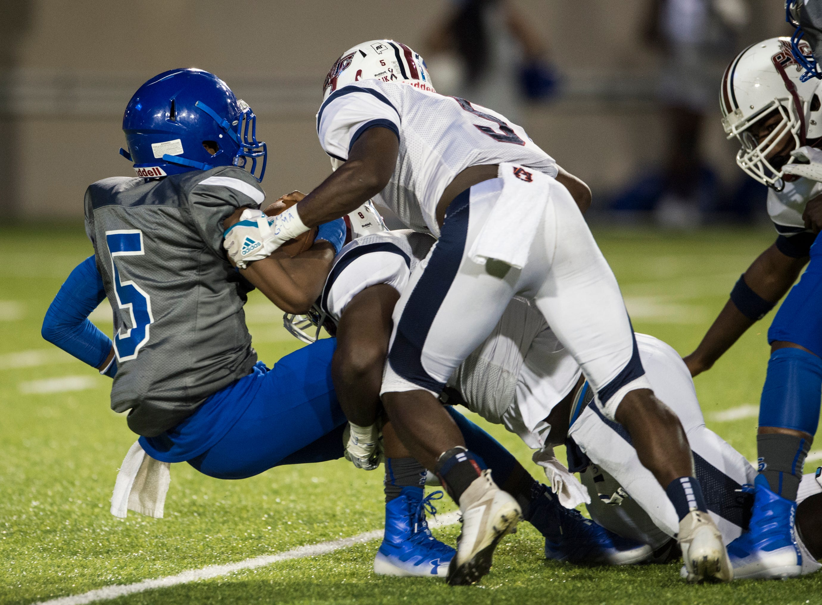 Lanier's Marquarius Moore (5) is taken down in the backfield by a swarm of Park Crossing defenders at Cramton Bowl in Montgomery, Ala., on Friday, Sept. 21, 2018. Lanier leads Park Crossing 14-7 at halftime.