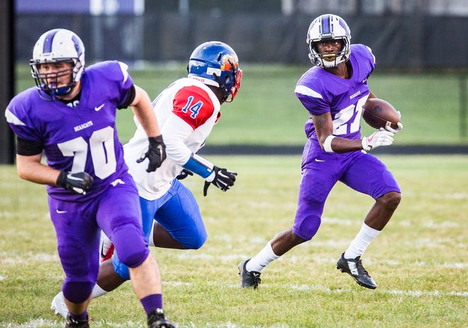 Central's Damarius Pegues runs against Kokomo with Victor Dennis (70) serving as lead blocker during their game at Central on Friday, Sept. 21, 2018.