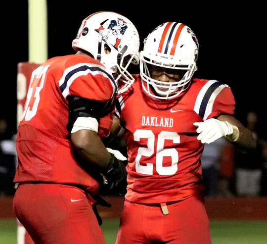 Oakland's Xavier Myers (26) celebrates his touchdown against Oakland with Jacob Crabill (53) on Friday, Sept. 21, 2018, at Oakland.