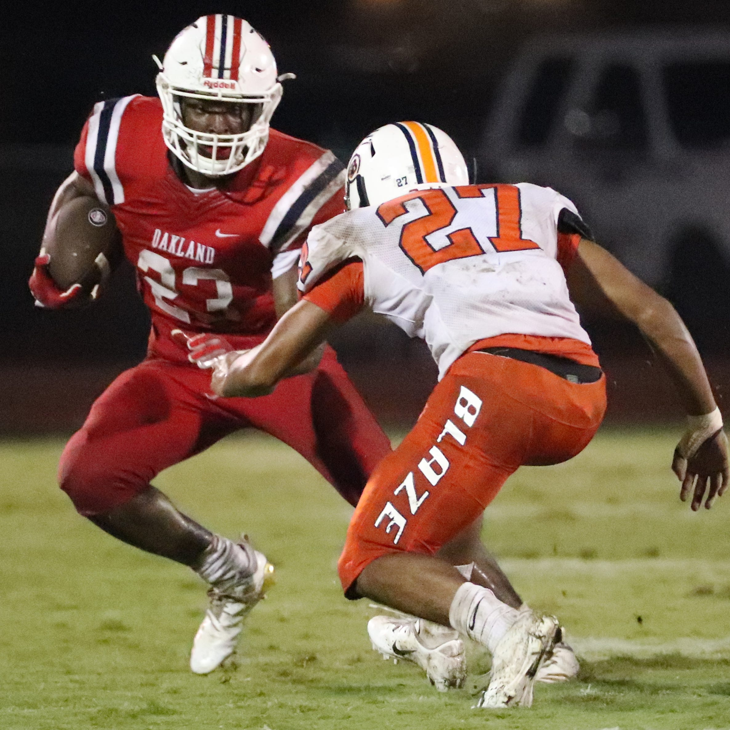 Oakland's BJ Connard (23) runs the ball as Blackman's Jalen Brown (27) moves in for a tackle on Friday, Sept. 21, 2018, at Oakland.