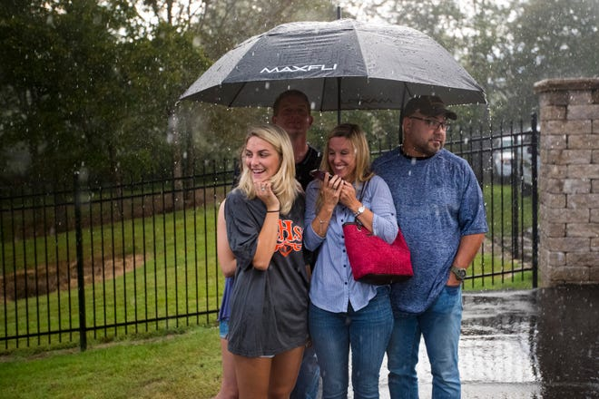 Jill Fuqua, left to right, Troy Fuqua, Angie Anderson and Brice Anderson try to stay dry as it starts to rain before Beech's game against Springfield at Beech High School in Hendersonville on Friday, Sept. 21, 2018. The stands were cleared due to lighting nearby before the game.