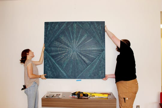 Art handlers install a piece by Nashville artist, Kelly S. Williams, at the Metro Courthouse.