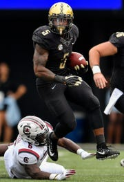 Vanderbilt running back Ke'Shawn Vaughn (5) leaps past South Carolina linebacker T.J. Brunson (6) during the first half at Vanderbilt University in Nashville, Tenn., Saturday, Sept. 22, 2018.