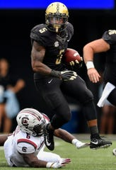 Vanderbilt running back Ke'Shawn Vaughn (5) leaps past South Carolina linebacker T.J. Brunson (6) during the first half at Vanderbilt University in Nashville, Tenn., Saturday, Sept. 22, 2018.