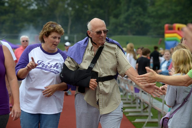 With his daughter Amy Houck, colon cancer survivor Don Forte high-fives supporters as Father Ryan High School hosts its 10th annual Relay for Life fund raiser for cancer research on Saturday.  Hundreds of cancer survivors, caregivers, family members and other supporters participated.