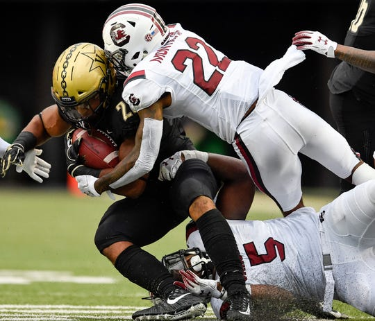 Vanderbilt running back Khari Blasingame (23) is tackled by South Carolina defensive back Steven Montac (22) and defensive lineman Keir Thomas (5) during the second half at Vanderbilt University in Nashville, Tenn., Saturday, Sept. 22, 2018.